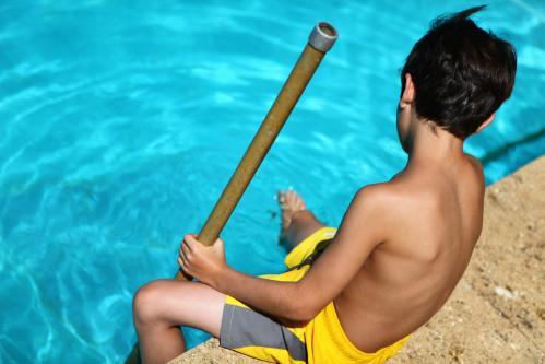 Un enfant au bord de la piscine avec un bracelet alarme
